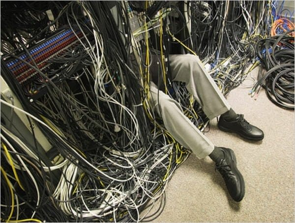 Photograph of hosting technician trying to fix messy data center.